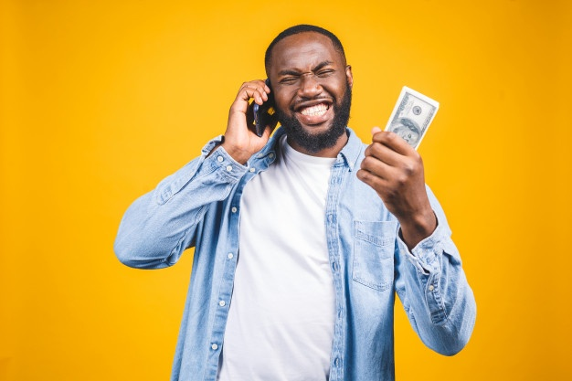 winner-young-rich-african-american-man-casual-t-shirt-holding-money-dollar-bills-mobile-phone-with-surprise_255757-1381
