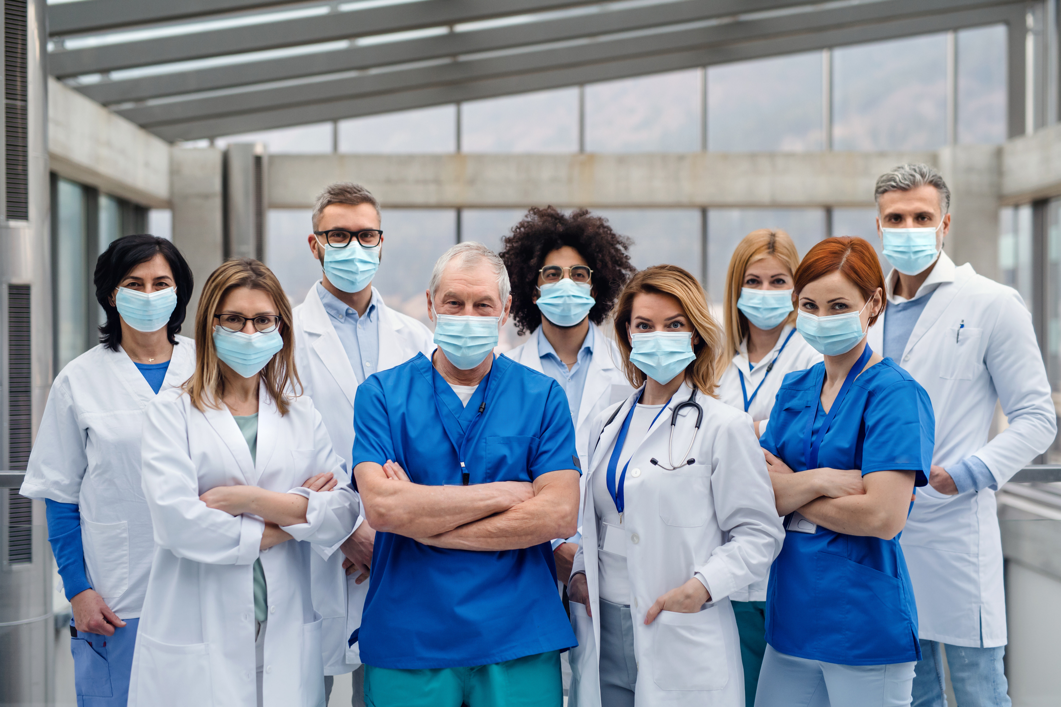 A group of doctors with face masks looking at camera, corona virus concept.